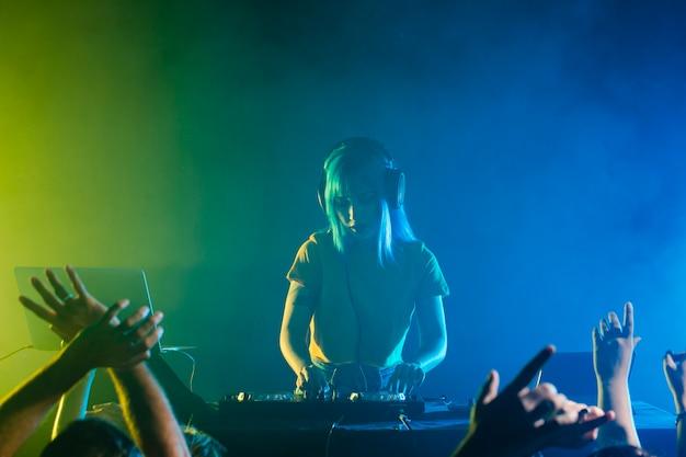 Clubbing mit einer dj-frau, die für die menge mixt