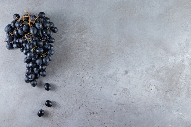 Cluster von frischen schwarzen trauben auf steinhintergrund gelegt.