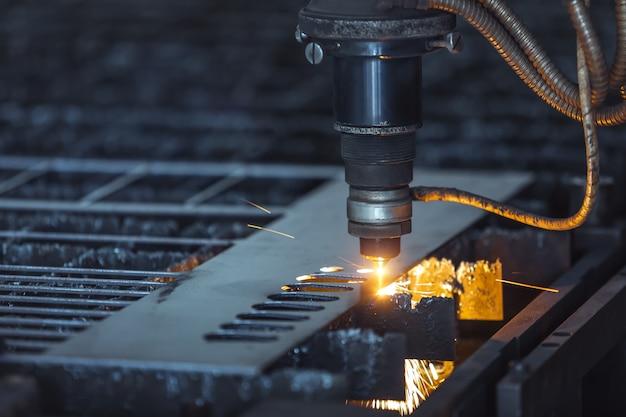 Cnc laserschneiden von metall, moderne industrietechnik. kleine schärfentiefe.