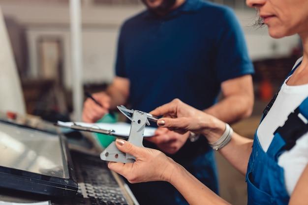 Cnc-maschinenbediener, der fertiges produkt überprüft
