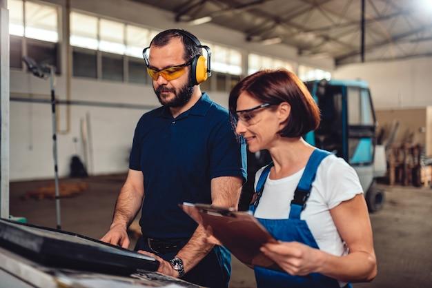 Cnc-maschinenbediener, die in der industriellen fabrikhalle arbeiten