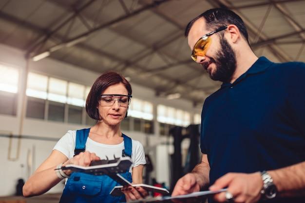 Cnc-maschinenbediener und supervisor messen ausgeschnittenes produkt