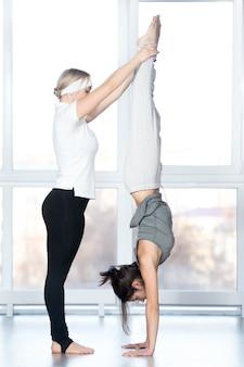Coach hilft dem schüler, handstand zu machen