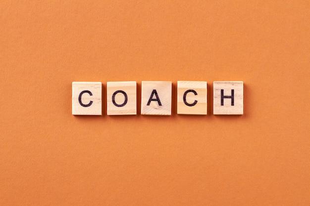 Coach ist ein spezialist, der sich mit mentoring beschäftigt. inspiration und motivation für das geschäft. buchstaben auf holzwürfeln lokalisiert auf orange hintergrund.