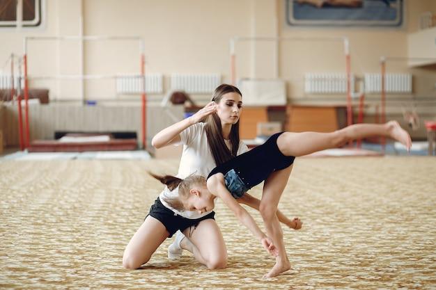 Coach mit student. mädchen turnerinnen, führt verschiedene gymnastikübungen und springen. kinder und sport, ein gesunder lebensstil.