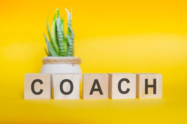 Coach-wort auf holzblock geschrieben. gelber hintergrund, konzept