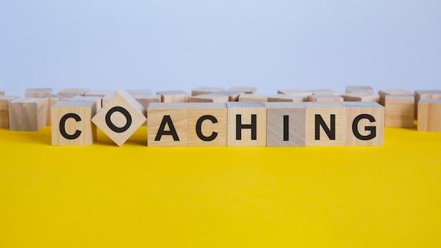 Coaching-wort auf holzblock geschrieben. reduktionswort besteht aus holzbausteinen, die auf dem gelben tisch liegen. geschäftskonzept