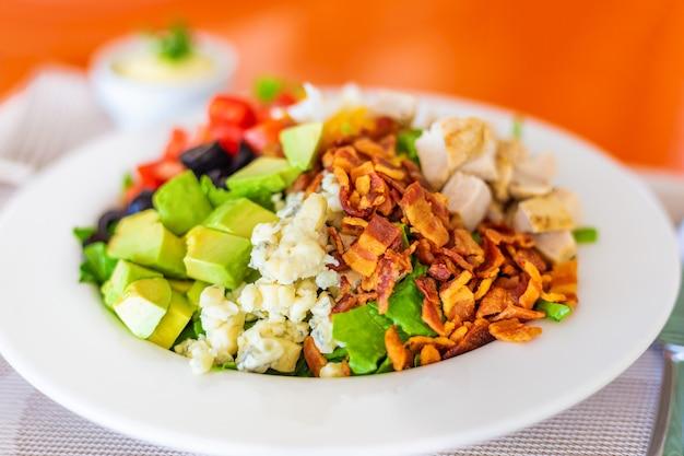 Cobb-salat auf weißem teller mit speck, blauschimmelkäse, gegrilltem hähnchen, gewürfelten geschnittenen tomaten und avocados