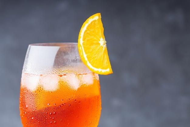 Cocktail-aperol-spritz. glas cocktail aperol spritz auf grauem hintergrund. italienischer sommercocktail mit einer orangenscheibe