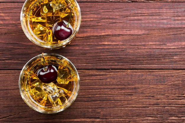 Cocktail aus whisky mit kirsche in zwei gläsern