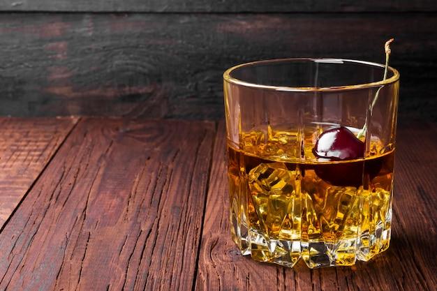 Cocktail aus whisky mit kirsche