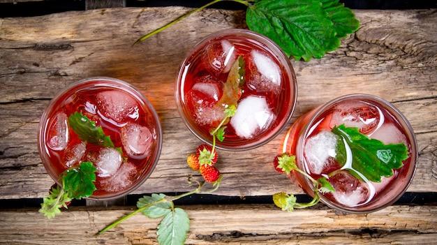 Cocktail erdbeere. ein cocktail von walderdbeeren mit eis auf einem holztisch. draufsicht