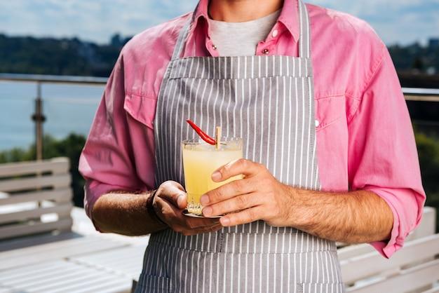 Cocktail für besucher. professioneller erfahrener kellner, der rosa hemd trägt, das cocktail für besucher bringt