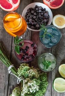 Cocktail gin tonic, mojito und aperol spritz mit minze, eis, limette, beeren, grapefruit und orange auf dem holzhintergrund.