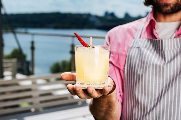 Cocktail im glas. professioneller erfahrener barmann, der alkoholcocktail im glas mit wenig pfeffer hält