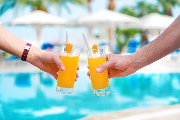 Cocktail in der hand am pool