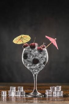 Cocktail in einem glas mit eis und kirsche.