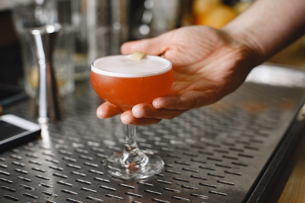 Cocktail in einem glas. rotes getränk. barista gießt einen drink ein.