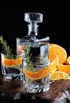 Cocktail klassischer dry gin mit tonic und orangenschale mit einem rosmarinzweig auf einem holzbrett mit saftigen orangenscheiben