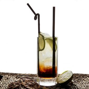 Cocktail kuba pintada von der seite mit tubuli für getränke und getrockneter zitrone und limette in servietten