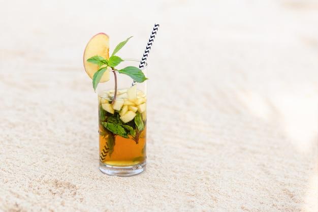 Cocktail mit apfel-, minz- und eiswürfeln im glas