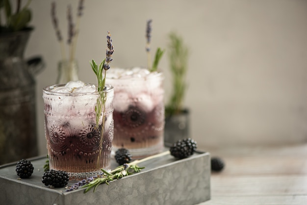 Cocktail mit beeren und lavendelsirup an einer hellen wand