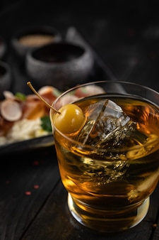Cocktail mit eis und kirsche auf einem dunklen tisch snacks für einen cocktail