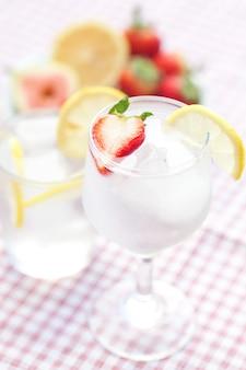 Cocktail mit eis, zitrone, feige und erdbeeren auf einem teller