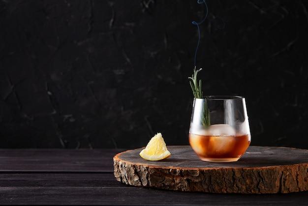 Cocktail mit eisrosmarin und zitrone auf holztisch