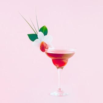 Cocktail mit erdbeeren, blumen und tropischen blättern dekoriert