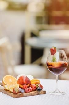 Cocktail mit geschnittenem obst auf einem hölzernen tablett