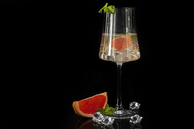 Cocktail mit grapefruit auf dunklem hintergrund mit einem zweig minze und eiswürfeln. isolieren. platz kopieren.