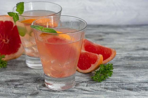Cocktail mit grapefruit auf hellem hintergrund mit einem zweig minze und eiswürfeln. isolieren. platz kopieren.