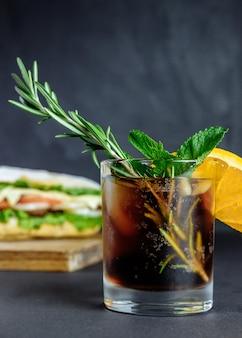Cocktail mit großem sandwich trinken street food, fast food. hausgemachte burger mit rindfleisch, käse auf dem holztisch. rosmarin, orange, minze glas cola mit eis, minze und zitrone auf schwarzem hintergrund