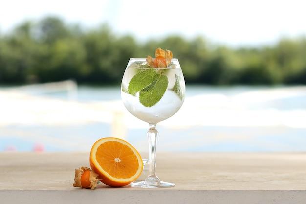 Cocktail mit minze und eis in einem glastrommel. mit blumen- und fruchtdekor