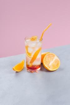 Cocktail mit orangenfruchtscheiben auf farbigem hintergrund