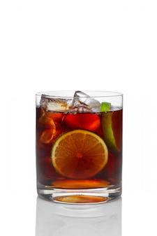 Cocktail mit rum und kolabaum mit eis, kalk und zitrone im altmodischen glas lokalisiert auf weiß