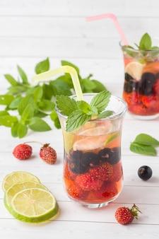 Cocktail mit schwarzer johannisbeere, erdbeere, minze und limette. abkühlendes sommergetränk.