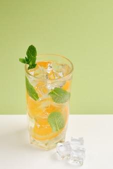 Cocktail mit zitrone und minze auf grünem hintergrund. platz kopieren.