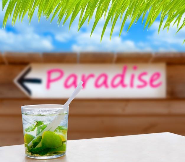 Cocktail mojito in einem schriftlichen paradieswort-pfeilzeichen