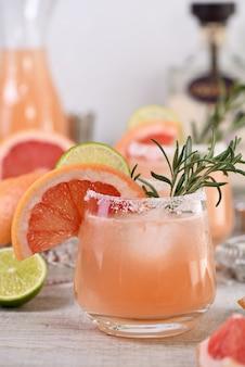 Cocktail pink palomas frische limette und rosmarin kombiniert mit frischem grapefruitsaft und tequila. ein festliches getränk ist ideal für brunch, partys und feiertage.