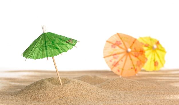 Cocktail regenschirm im sand auf weißem hintergrund