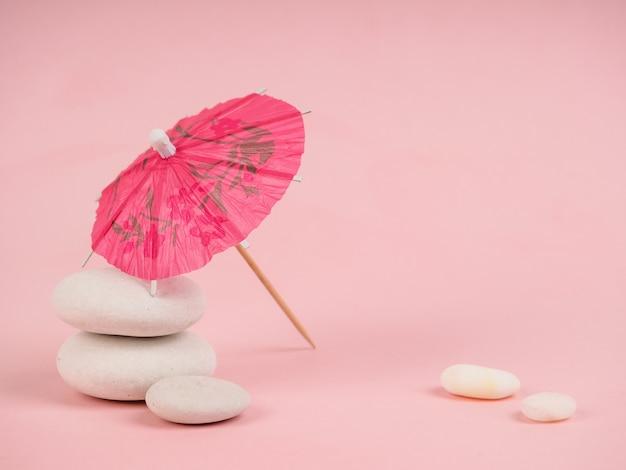 Cocktail regenschirm. rosa papiercocktailregenschirm lokalisiert auf rosa. papier rosa regenschirm auf rosa steinen, in der nähe von weißen steinen, das konzept der freizeit und minimalismus