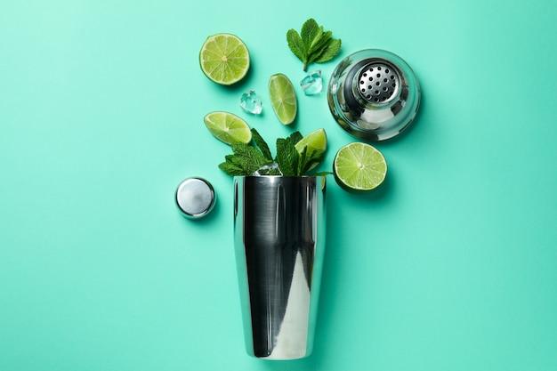 Cocktail shaker und zutaten für mojito auf minzhintergrund