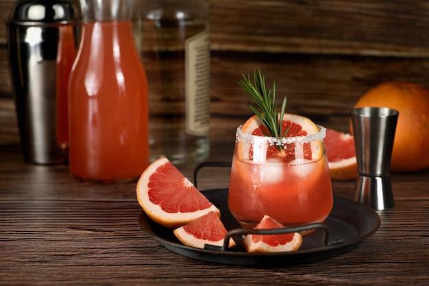 Cocktail tequila frischer grapefruitsaft kombiniert und rosmarin. ein festliches getränk ist ideal für brunch, partys und feiertage.