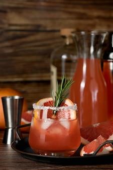 Cocktail tequila frischer grapefruitsaft kombiniert und rosmarin. festliches getränk ist ideal für brunch, partys und feiertage.