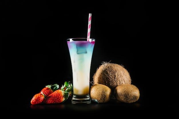 Cocktail und früchte auf schwarzem hintergrund