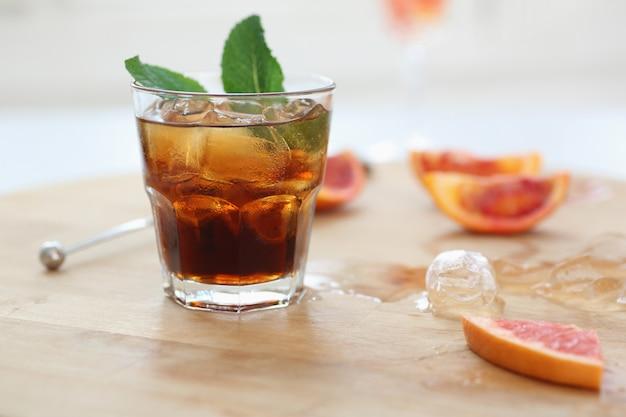 Cocktail whisky cola mit eis in einem glas. auf einem holzbrett liegen fruchtfragmente. foto mit schärfentiefe.