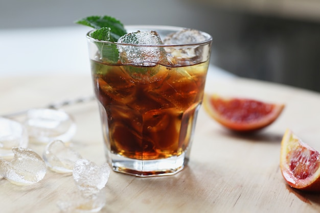 Cocktail whisky cola mit eis in einem glas. auf holzbrett sind fruchtfragmente.