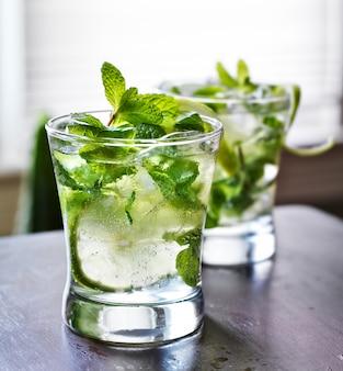 Cocktail - zwei kalte mojitos auf holztischplatte